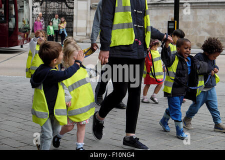 Nursery school children & childminder wearing high visibility fluorescent safety jackets hold hands on walk in a - Stock Photo