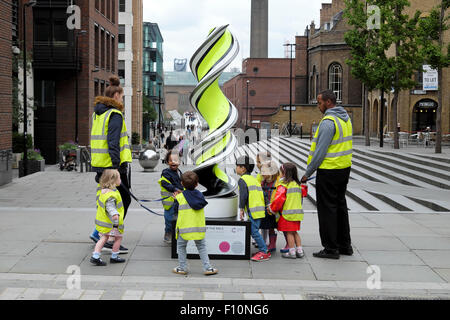 Nursery school age children with childminders wearing high visibility fluorescent jackets on walk in London UK  - Stock Photo