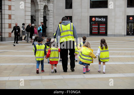 Nursery school children walking with childminders wearing high visibility fluorescent safety jackets on a street - Stock Photo