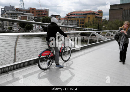 A young man rides a Santander hire bike over the Millennium Bridge in London UK  KATHY DEWITT - Stock Photo