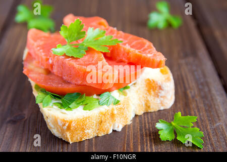 Sandwich with salmon (trout), cream cheese, tomato and parsley on rustic wooden background close up - Stock Photo