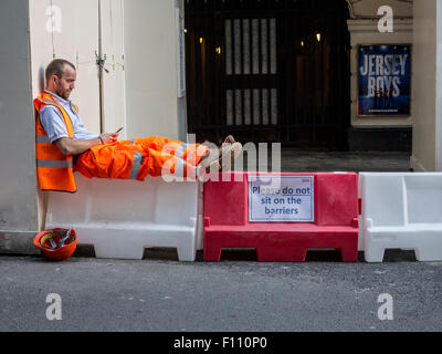 A man sitting on some barriers above a sign that says Please do NOT sit on the barriers - Stock Photo