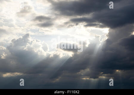 Shafts of sunlight shining through dark cloud - Stock Photo