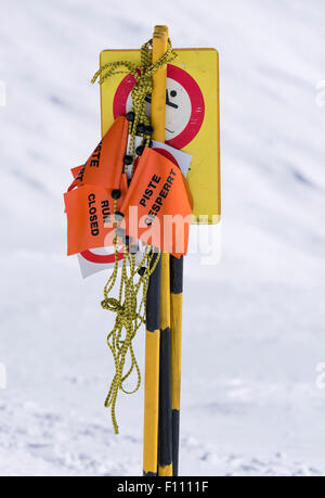 'Ski run closed' sign and barrier tape on a ski piste in the Swiss alps (Blatten/Belalp, canton Valais). - Stock Photo
