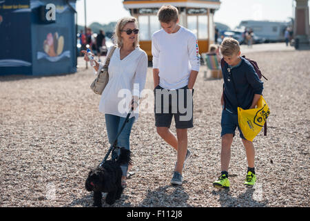 A mother and her two teenage sons walk along a shingle beach in Portsmouth with their black cockapoo dog - Stock Photo