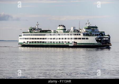 ferry boat Spokane crosses Puget Sound from Kingston to Edmonds Washington on an early midsummer evening as sky - Stock Photo