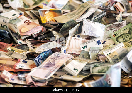Money background of a heap of assorted banknotes in different currencies - Stock Photo