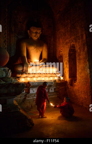 Asian monks-in-training lighting candles at Buddha shrine - Stock Photo