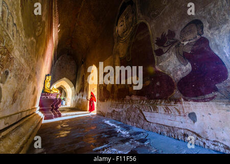 Asian monk-in-training walking in dilapidated stone temple - Stock Photo