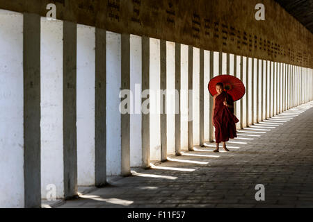Asian monk-in-training carrying parasol in hallway - Stock Photo