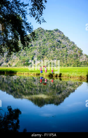 Asian family walking past still lake in rural field - Stock Photo