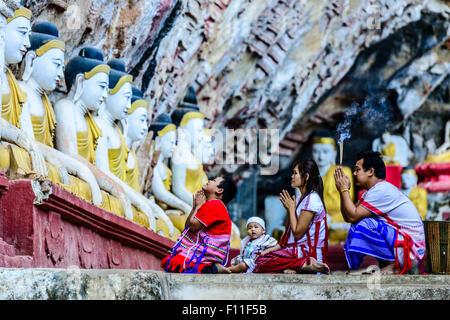 Asian family praying at Buddha temple - Stock Photo