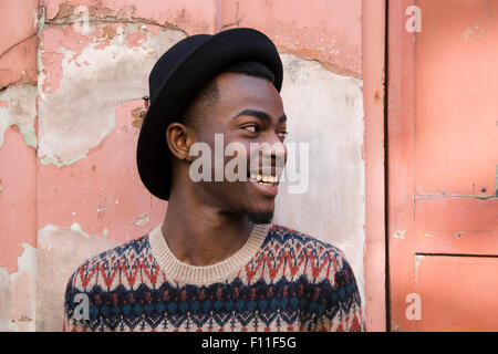 Black man sitting by dilapidated building - Stock Photo
