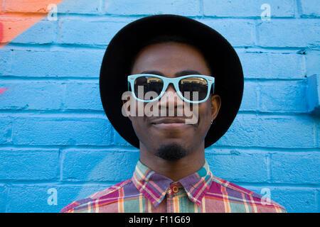 Black man wearing sunglasses near colorful wall - Stock Photo