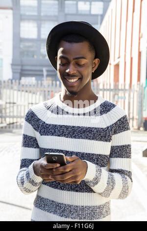 Black man using cell phone on urban sidewalk - Stock Photo