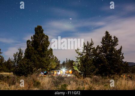 Campsite in remote field under cloudy sky