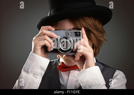 Close up of boy in top hat photographing with vintage camera - Stock Photo