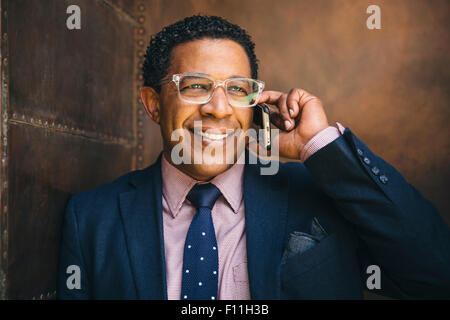 Mixed race businessman talking on cell phone - Stock Photo
