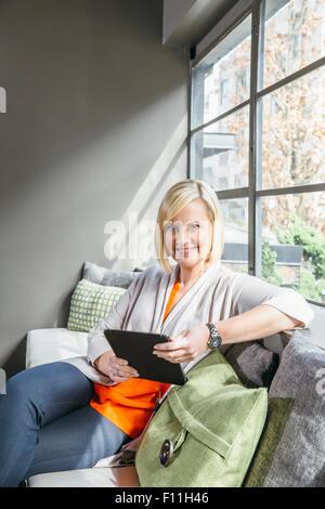 Caucasian businesswoman using digital tablet in office lobby