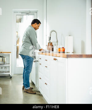 Mixed race man washing dishes in kitchen - Stock Photo
