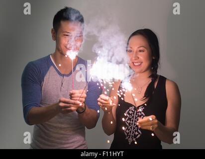 Smiling couple playing with sparklers - Stock Photo