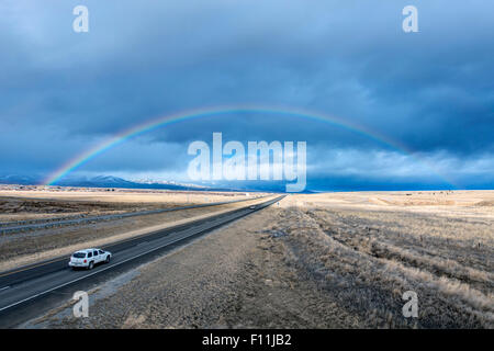 High angle view of car driving to rainbow on remote road - Stock Photo