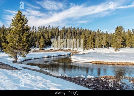Snowy fields and hills near remote stream - Stock Photo