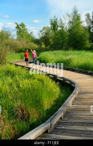 Children walking on wooden walkway in wetland marsh - Stock Photo