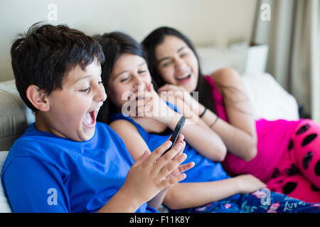 Hispanic siblings using cell phone on sofa - Stock Photo