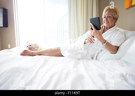 Older Caucasian woman using digital tablet on bed - Stock Photo