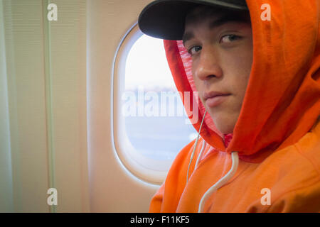 Caucasian man wearing hoodie on airplane - Stock Photo
