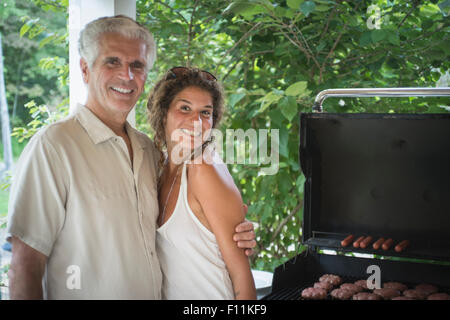 Caucasian father and daughter grilling in backyard