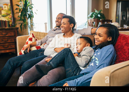 Black family watching television on sofa - Stock Photo