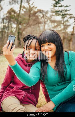 Black sisters taking selfie outdoors Stock Photo
