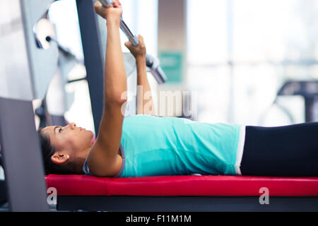 Beautiful woman work out with barbell on the bench in fitness gym - Stock Photo