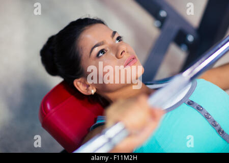 Young sports woman workout with barbell on the bench in fitness gym - Stock Photo