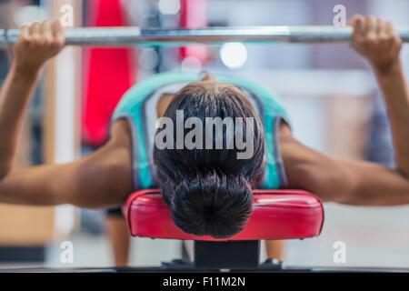 Young woman workout with barbell on the bench in fitness gym - Stock Photo