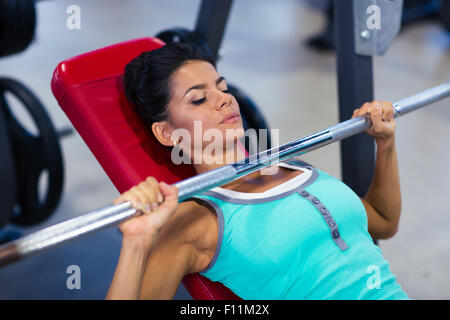 Attractive sports woman workout with barbell on the bench in fitness gym - Stock Photo