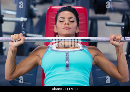 Beautiful woman lifting barbell on the bench in fitness gym - Stock Photo