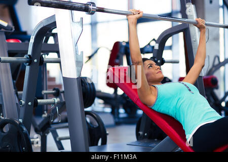 Beautiful woman doing exercises with barbell on the bench in fitness gym - Stock Photo