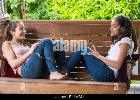 Teenage girls listening to music on porch swing - Stock Photo