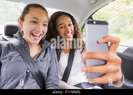 Teenage girls using cell phone in car back seat - Stock Photo
