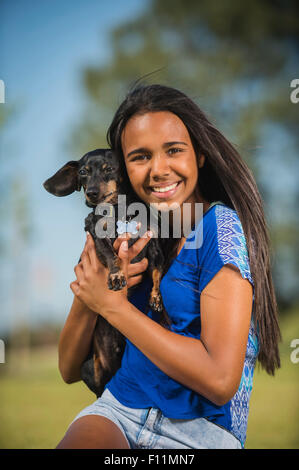 Mixed race girl hugging dog outdoors - Stock Photo