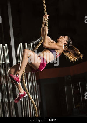 Caucasian athlete climbing rope in gym - Stock Photo