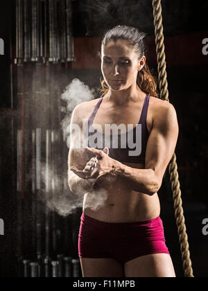 Caucasian athlete chalking her hands in gym - Stock Photo