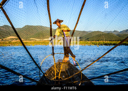 Asian fisherman using fishing net in canoes on river - Stock Photo
