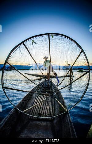 Asian fisherman using fishing net in canoe on river - Stock Photo