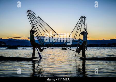 Asian fishermen using fishing nets in canoe on river - Stock Photo