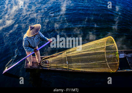 High angle view of Asian fisherman using fishing net in canoe on river - Stock Photo