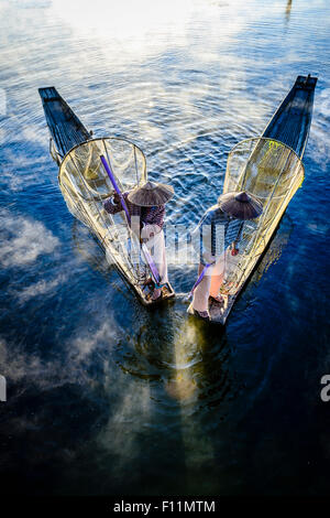 High angle view of Asian fishermen using fishing nets in canoe on river - Stock Photo